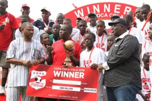 Dr. Ademola Are, Director, Grassroots, Youth and Sports, representing the Minister for Sports; Adeola Adetunji, Managing Director, Coca-Cola Nigeria; and Barrister Seyi Akinwunmi, Vice-President 1, Nigeria Football Federation (NFF); presenting the 2016 Copa Coca-Cola U-15 winners, Asegun Comprehensive High School, Oyo State presented with a cheque of One Million Naira.